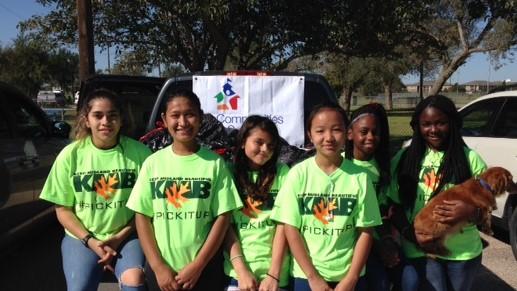 Students wearing green shirts smiling at camera.